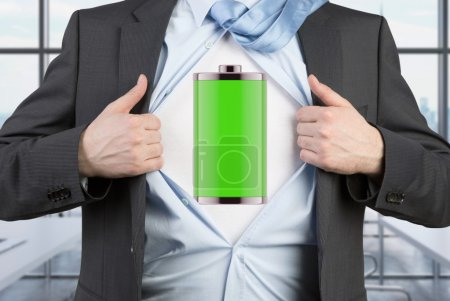 A man in a suit is tearing the blue shirt. Full charged battery on the chest. Modern panoramic office background.