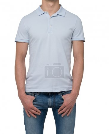 A man in a light blue polo shirt and denims holds his hands in pockets. Isolated on white.