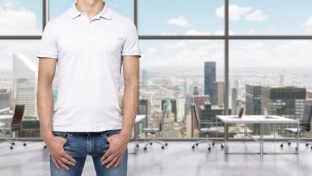 A man in a white polo shirt and denims holds his hands in pockets. A modern panoramic office space in New York City. Manhattan panoramic view.