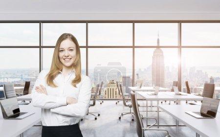 Photo pour Sourire belle femme d'affaires avec les mains croisées est debout dans un bureau panoramique moderne à New York. Manhattan sunset view. Image teintée - image libre de droit