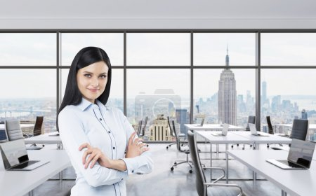 Smiling brunette business lady with cross hands is standing in a modern panoramic office in New York City. Manhattan panoramic view. Workplaces are on the office open space behind the model.