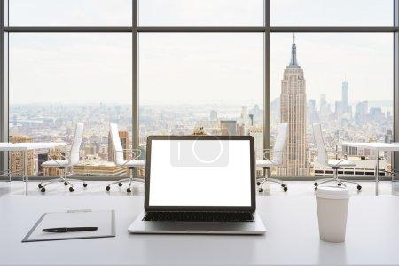 Photo pour Vue de face du lieu de travail dans un bureau panoramique moderne à New York. tables blanches et chaises blanches. Un ordinateur portable avec un écran blanc, bloc-notes et une tasse de café sont sur la table. rendu 3d. - image libre de droit