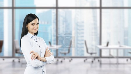 A side view of a beautiful smiling lady with crossed hands. The brunette woman is dressed in formal clothes. Modern workplaces in a fancy panoramic office in Singapore.