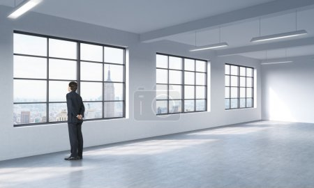 A full length man in formal suit who is looking out the window, New York panoramic view. A modern loft style open space.