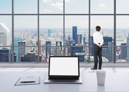Photo pour Une personne vêtue de vêtements formels est debout dans le bureau panoramique moderne et regardant New York. Un ordinateur portable avec écran blanc, un pavé d'écriture et une tasse de café sur la table blanche. - image libre de droit