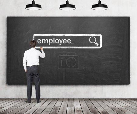Photo for A handsome recruiter is writing down the word employee into the virtual searching bar in the black chalk board. The Internet concept of searching available candidates. - Royalty Free Image