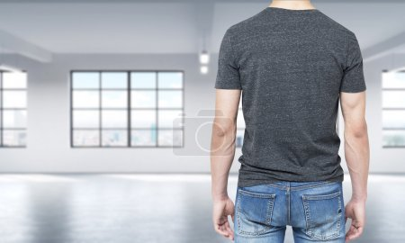 Rear view of the man in grey t-shirt and denims. Modern loft style open space on the background.