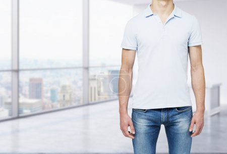 A man in a polo shirt and denims stands in modern panoramic office with New York city view.