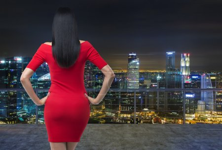Photo for Rear view of gorgeous brunette in red dress posing on modern roof terrace with evening panoramic New York cityscape. - Royalty Free Image