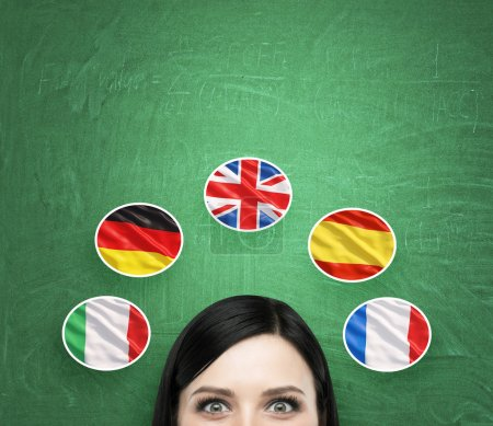 A concept of foreign language studying process. A foreseen of the brunette girl surrounded by icons of european flags. Green chalkboard background.