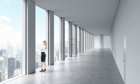 A woman in formal clothes is looking out the window. Empty modern bright clean interior of an open space office. Huge panoramic windows with New York view.