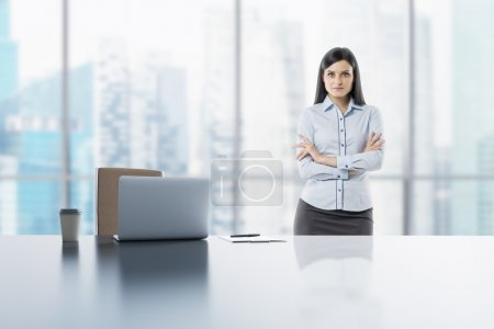 A young brunette lady with crossed hands in the modern panoramic office in Singapore. A laptop, notepad and a coffee cup are on the white table.