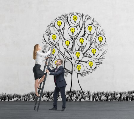 A man in formal suit holds a ladder for the business lady who climbs up the sketched tree with light bulbs. Concrete background.