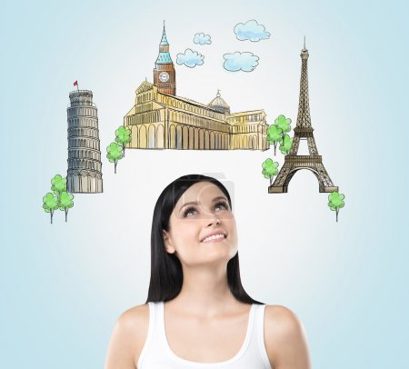A beautiful brunette is looking up by dreaming about the visiting of the most famous european cities. The concept of tourism and sightseeing. Light blue background.