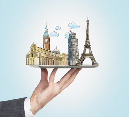 A man's hand holds a tablet with sketches of the most famous places in Italy, Great Britain and France. The concept of tourism and sightseeing. Light blue background.