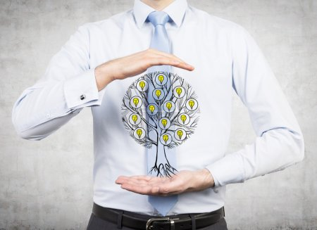 A close up of a man's body in formal shirt and tie who holds a sketched tree with light bulbs between his hands.