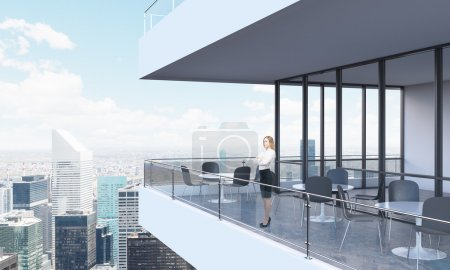 A woman is looking at New York standing on the terrace in a modern skyscraper with panoramic windows.