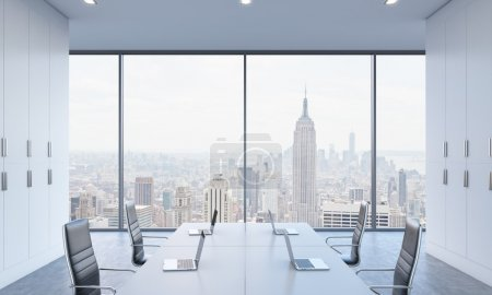 Workplaces or conference area in a bright modern open space office. White tables equipped by modern laptops and black chairs. New York view. 3D rendering.