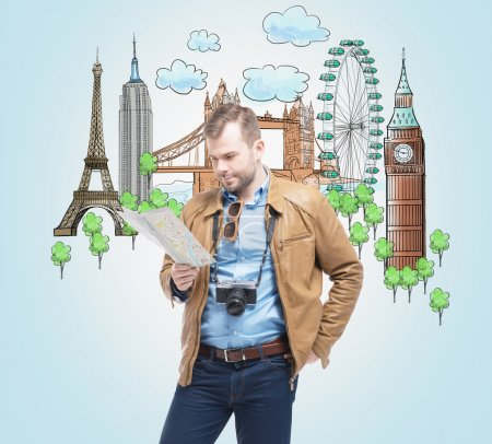 A handsome tourist in casual clothes with camera trying to find a location in the map. Drawn sketches of the most famous touristic places on the light blue background. The concept of tourism.