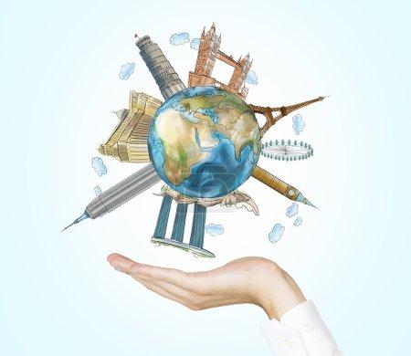 Photo pour Une main tient un globe avec esquissées lieux les plus célèbres dans le monde. Un concept de tourisme et le tourisme. fond bleu clair. Les éléments de cette image fournie par la Nasa. - image libre de droit