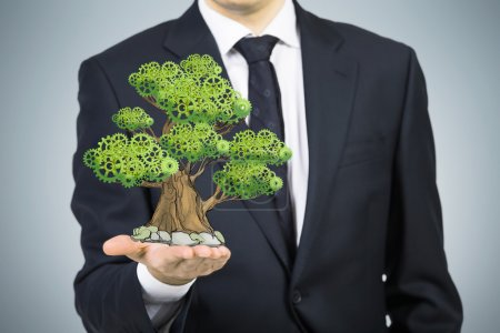A person in formal suit holds a sketched tree on the palm. Light grey background. A concept of the business development.