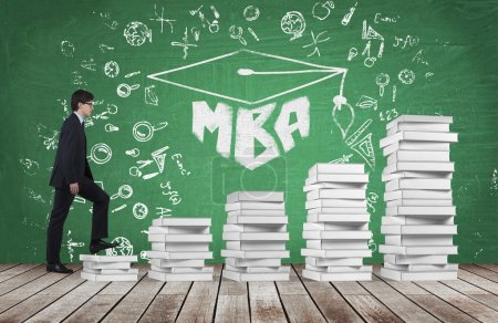 A man is going up using a stairs which are made of white books to reach graduation hat. The written word MBA is drawn on the green chalkboard which symbolises a professional business education.