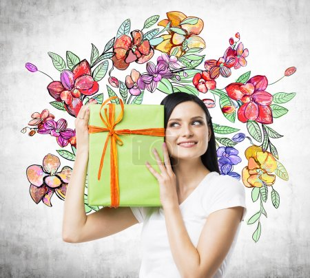 A curious brunette woman tries to guess what is inside the green gift box. The sketch of colourful flowers is drawn on the concrete wall.