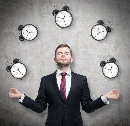 Meditative businessman is pondering about time management. The person in formal suit is surrounded by alarm clocks. There is a concrete wall in the room.