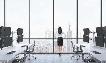 Rear view of a lady in formal suit who is looking out the window in the modern panoramic office with New York view. White tables equipped with modern trader's stations and black chairs.