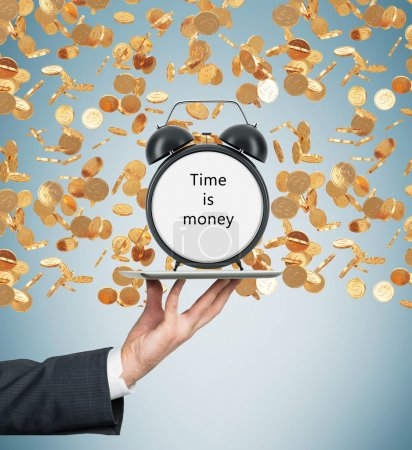 Photo for A hand holds a tablet with alarm clock. Golden coins are falling down from the ceiling. The concept of time is money. Light blue background. - Royalty Free Image