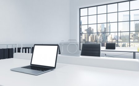 Workplaces in a bright modern loft open space office. Tables equipped with laptops, white copy space in the screen. Docs shelves. New York view in the panoramic windows. 3D rendering.