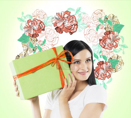 A curious brunette woman tries to guess what is inside the green gift box. The sketch of colourful flowers is drawn on the light green wall.