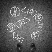 Top view of the formal man's black shoes and drawn arrows with exclamation and question marks on asphalt.