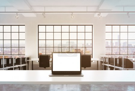 A workplace in a bright modern office. A working desk is equipped with a modern laptop with white copy space in the screen. Docs shelves. New York view in the windows. Toned image. 3D rendering.