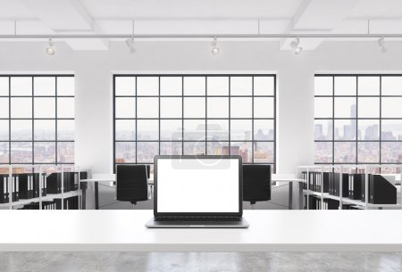 A workplace in a bright modern loft open space office. A working desk is equipped with a modern laptop with white copy space in the screen. Docs shelves. New York view in the windows. 3D rendering.