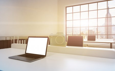 Workplaces in a bright modern loft open space office. Tables equipped with laptops, white copy space in the screen. Docs shelves. White copy space in the panoramic windows. 3D rendering. Toned image.