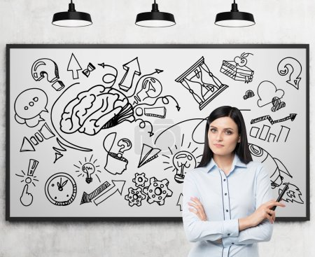 A beautiful brunette professional is thinking about business development. A business development or brainstorm sketch is drawn on the whiteboard behind the person.