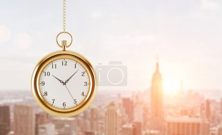 A model of pocket watch which is hanging on the chain. A concept of a value of time in business. A sunset panoramic New York view. 3D rendering. Toned image.