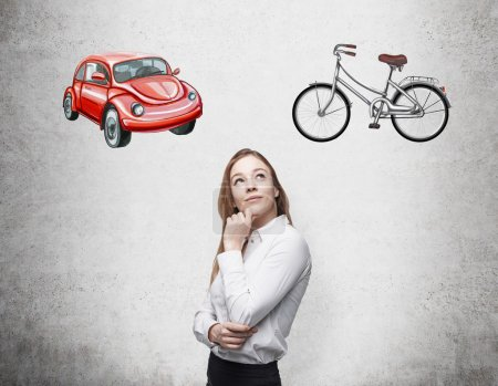 A beautiful woman is trying to chose the most suitable way for travelling or commuting. Two sketches of a car and a bicycle are drawn on the concrete wall.