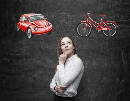 A beautiful woman is trying to chose the most suitable way for travelling or commuting. Two sketches of a car and a bicycle are drawn on the black chalkboard background.