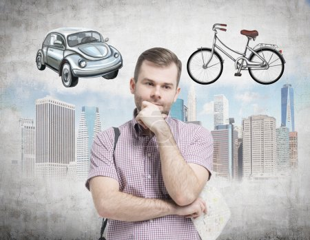A handsome man in casual shirt is trying to chose the most suitable way for travelling or commuting in the city. Sketches of a car, a bicycle and New York city are on the concrete background.