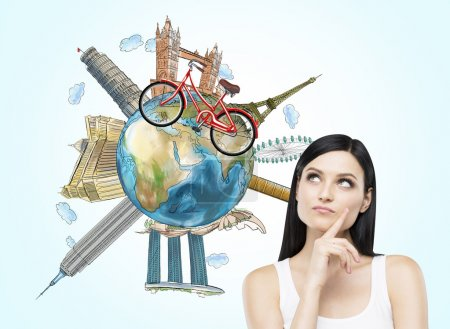 A brunette woman is dreaming about travelling. The globe with the most famous places in the world. A model of bicycle crosses of the globe. Travelling. Elements of this image furnished by NASA.