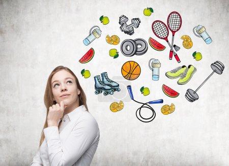 Photo pour Rêvant de belle dame pense à son choix d'activités sportives. Icônes de sport colorés sont dessinés sur le mur de béton. Un concept d'un mode de vie sain. - image libre de droit