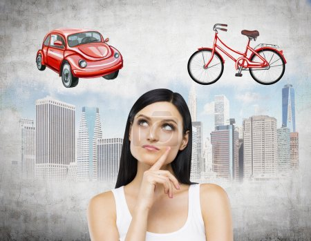 A brunette lady is trying to chose the most suitable way for travelling or commuting in the city. Sketches of a car, a bicycle and New York city are on the concrete background.