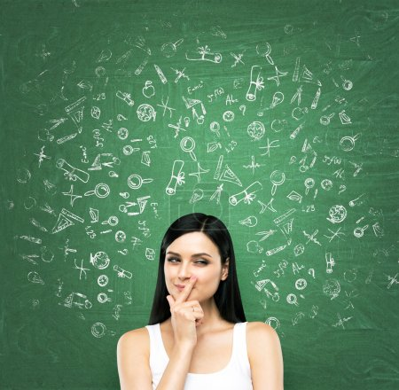 A portrait of a young artful brunette lady who is thinking about advantages of education. The lady is in a white tank top. Educational icons are drawn on the green chalkboard.