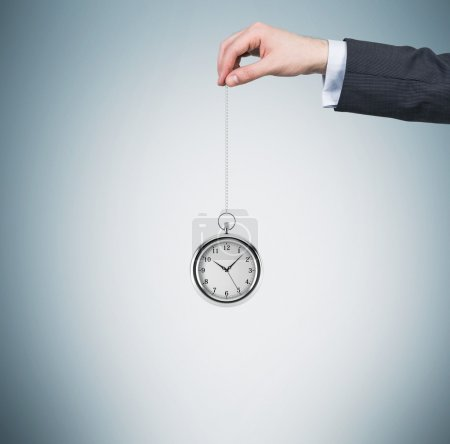 A hand holds a pocket watch in a chain. Light blue background. Time is money concept.