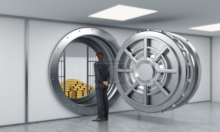 Photo pour Young man standing in front of a big unlocked round metal safe in a bank with a pyramid of gold bars and lock-boxes inside, a concept of security and client service depository. - image libre de droit
