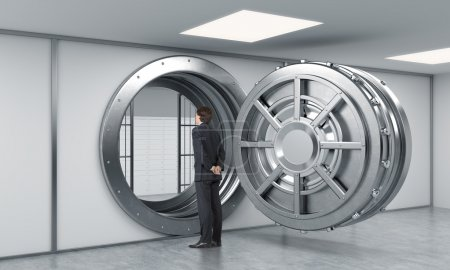 Photo pour Young man standing in front of a big unlocked round metal safe in a bank with lock-boxes inside in a depository with his back half turned looking inside,  a concept of security and aspirations - image libre de droit