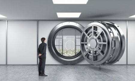 Photo pour Young man standing in front of a big unlocked round metal safe in a bank with lock-boxes and heaps of dollars inside, in a depository, with his back half turned looking inside, a concept of aspiration - image libre de droit