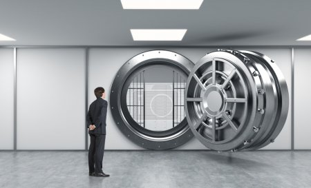 Photo pour Young man standing in front of a big unlocked round metal safe in a bank with lock-boxes inside in a depository with his back half turned looking inside,  a concept of aspirations - image libre de droit